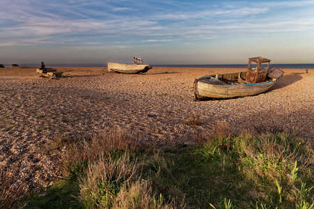 shingle beach: Empty shingle beach with old, abandoned fishing boats
