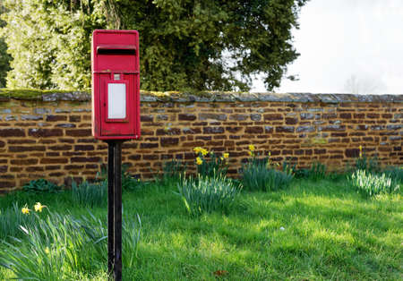 post box: Traditional English post box with green grass and stone wall in background