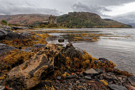 Distant view od Eilean Donnan castle with rocks and loch in a foreground with focus on the castle and its surrounding