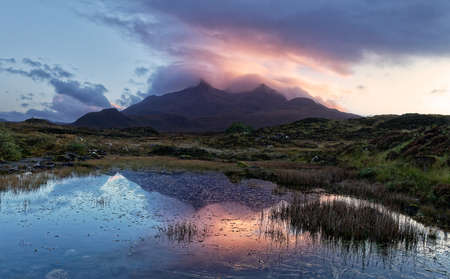 Beautiful, very colorful sunset over Black Cuillin mountains on Isle of Skye in Scotland - stunning sky reflected in the water with darker silhouette of the peaks Archivio Fotografico