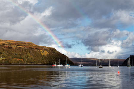 Portree bay with small boats and stunning rainbow over them