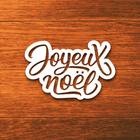 joyeux: Joyeux Noel text on paper label with hand lettering over wood background. Merry Christmas sticker or greeting card vector design template with french inscription