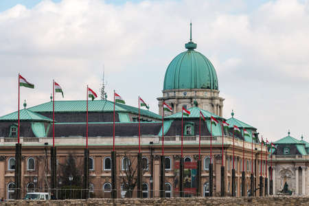 hungarian: Budapest, Hungary - March 09, 2017: National hungarian waving flags in front of Royal palace building in Buda castle Editorial