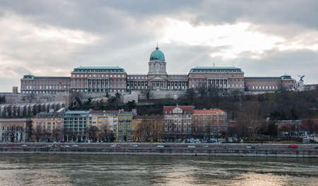 Budapest, Hungary - Scenic view of cityscape with the river Danube and front facade of royal palace building on hill in Buda castle