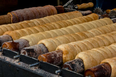 Trdelnik or trdlo national czech street food baked in Prague. Close-up of cooking sweet dessert for tourists Stock Photo