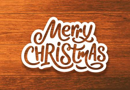 Merry Christmas text on paper label with hand lettering over wood background. Sticker or greeting card vector design template for Xmas celebration
