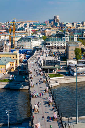 Moscow, Russia - April 30, 2019: Cityscape with Patriarchal bridge, Moscow river and city buildings on the background in sunny day. Aerial view to pedestrian bridge with tourists Redakční