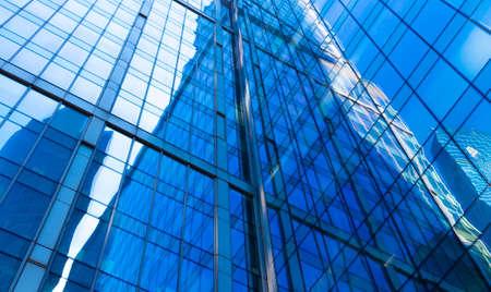 Reflexion über Glasfassaden des modernen Wolkenkratzers am sonnigen Tag. Konzept des geschäftlichen Hintergrunds mit Architekturdetails des Finanzviertelgebäudes