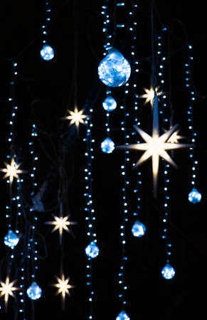 Christmas lights. Glowing garland with hanging stars and balls at night black background