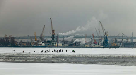 City landscape in winter. Fisherman group on ice in frozen harbor and industrial port with cranes on the background. Saint-Petersburg cityscape