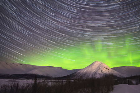 Star Trails on Night Sky and Green Northern Lights in Snowy Mountains at Winter Night.