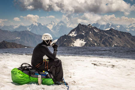 Mountaineer man sitting on a backpack, keeping a cup in hands an