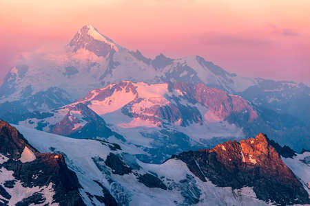 Colorful pink sunrise in mountains. Caucasus, Russia.