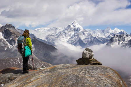 Young Woman hiker with backpack and hiking poles is standing and looking on Ama Dablam mountain. Cloudy sky. Himalaya, Nepal. Stock Photo