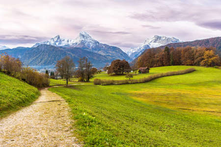 Green bright meadow, path and famous Watzmann mountain on a background. Bavarian alps. Germany