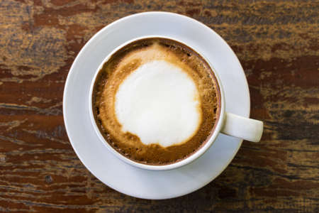 A white cup of cappuccino on saucer and on brown wooden table. Top view.