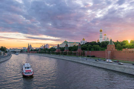 Moscow Kremlin and Moscow River with ships at sunset. Cars traffic on embankment and cloudy sky. Russia.