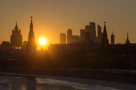 Moscow Kremlin and Moscow City Business Center Silhouette at Sunset. Sun in Frame. Russia.