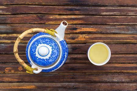 Blue teapot and cup of chinese green tea on wooden brown table. Top view.