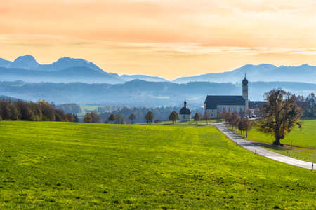 Green colorful meadow, road, chapel, church and mountains in misty autumn morning. Alpine landscape, Bavarian alps, Germany.