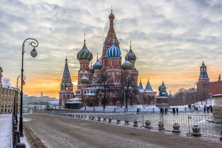 Saint Basils Cathedral in Red Square at winter morning. Road, light poles and colorful sky. Moscow, Russia.