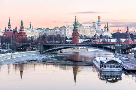 Moscow Kremlin and Moscow river in winter morning. Pinkish and golden sky with clouds. Russia