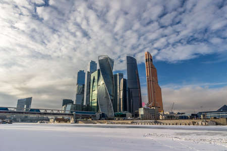 Skyscrapers of Moscow city business center in winter, frozen Moscow river and blue sky with clouds.