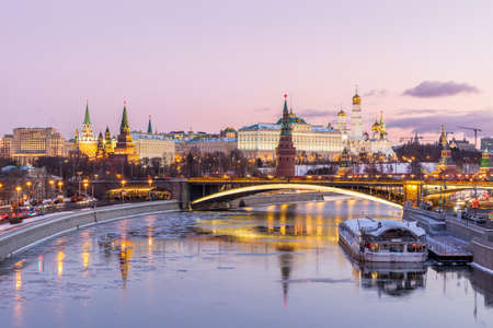 Illuminated Moscow Kremlin in winter morning. Pink sunrise and sky with clouds. Russia
