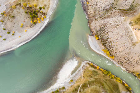 The confluence of Chuya and Katun rivers in Autumn. Aerial Top-Down View. The Altai Mountains, Russia.