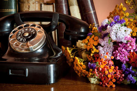 old phone with bouquet on desktop Stock Photo