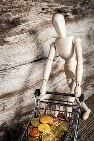 wooden mannequin with shopping cart with coins