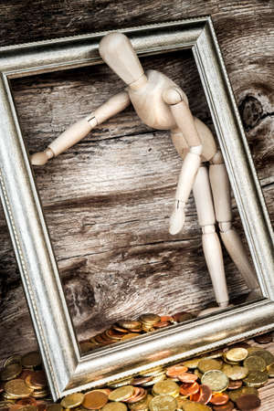 wooden mannequin with coins - concept Archivio Fotografico