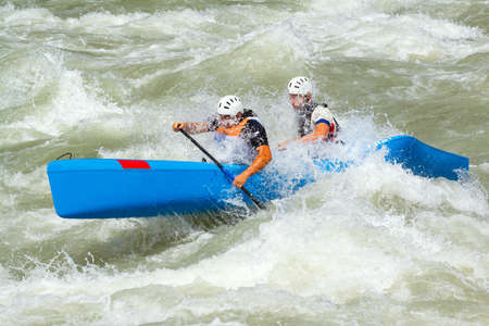 couple of downhill athletes with kayaks among rapids