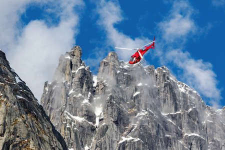 red helicopter flying over the alps