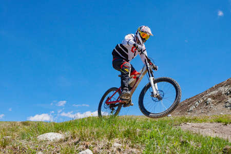 athlete running downhill with mountain bike in the high mountains