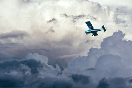 airplane in the clouds in stormy sky