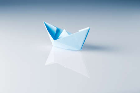 paper boat with reflection on shiny surface