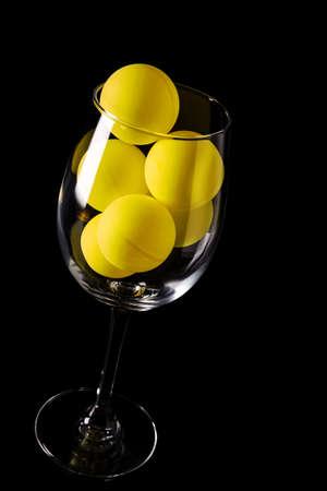 Glass goblet with yellow balls Archivio Fotografico