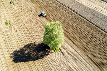 Tractor at work in plowed field, aerial view
