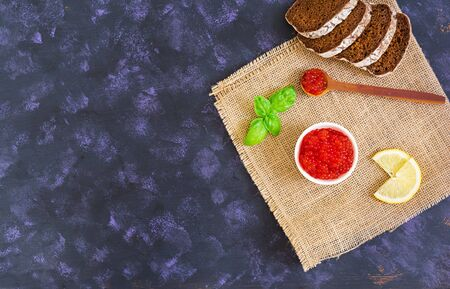 Red caviar on dark background. Top view.