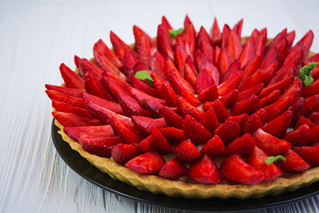 Delicious tart with strawberry on wooden background Stock fotó