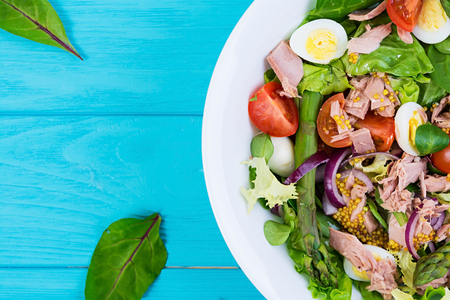 Salad with tuna, tomatoes, quail eggs, asparagus and onions on wooden background Banco de Imagens