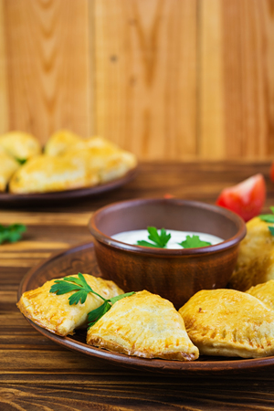 Delicious baked empanadas on wooden background Stock Photo