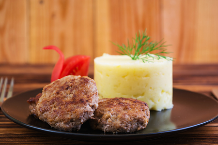 Puree potatoes with cutlets on wooden background Stock Photo