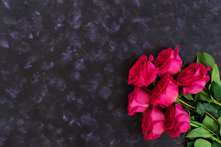 Bouquet of pink roses on dark background. Top view