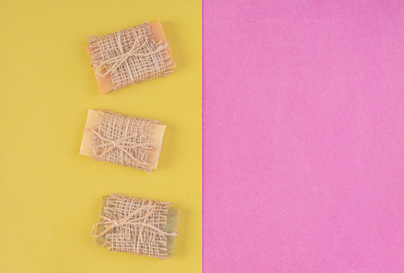 Hand made soap bars on pink-yellow background. Top view. Mockup for design