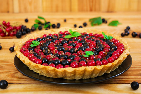 Delicious tart with custard and currant on wooden background