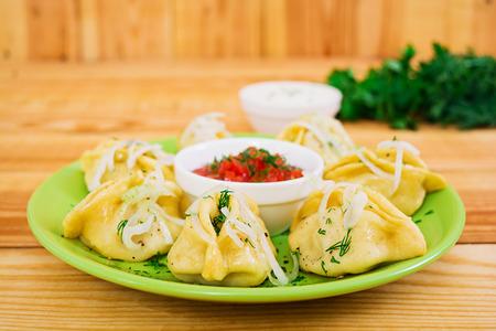 Delicious manti dumplings on wooden background