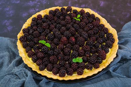 Delicious tart with blackberries on dark background