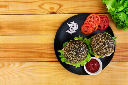 Handgemachter Burger auf dunklem Hintergrund. Leckerer schwarzer Burger
